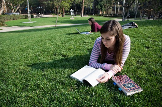 Stock Photo: 1610-198 Close-up of a young woman reading a textbook on a lawn