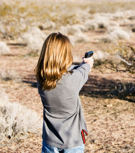 Rear view of a woman aiming with a handgun : Stock Photo