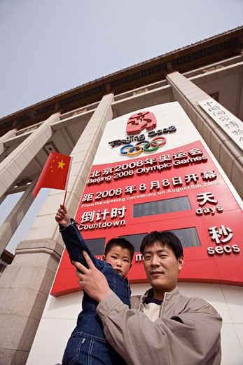 Low angle view of a mid adult man with his son in front of an Olympic Countdown Board, Beijing, China : Stock Photo