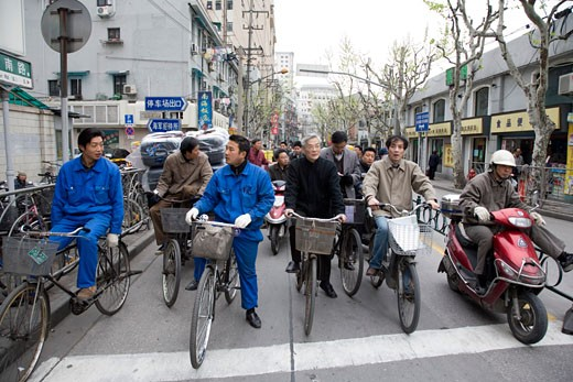 Group of people riding bicycles on a road, Shanghai, China : Stock Photo