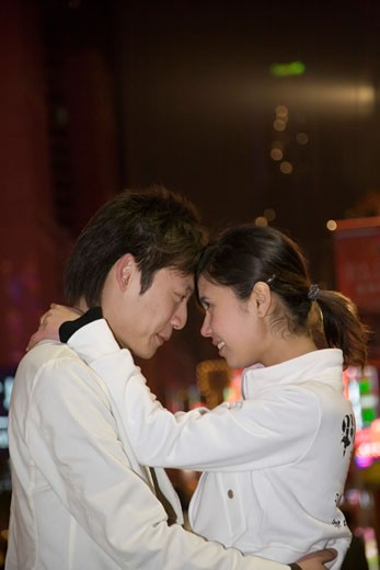 Side profile of a young couple embracing each other, Shanghai, China : Stock Photo