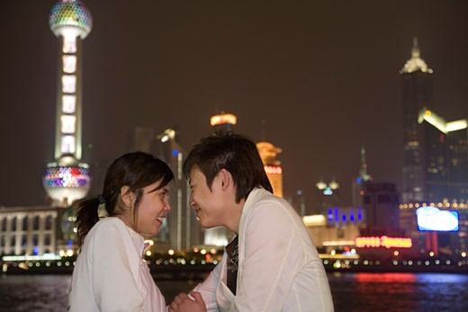 Stock Photo: 1610-295D Side profile of a young couple smiling at each other, Shanghai, China