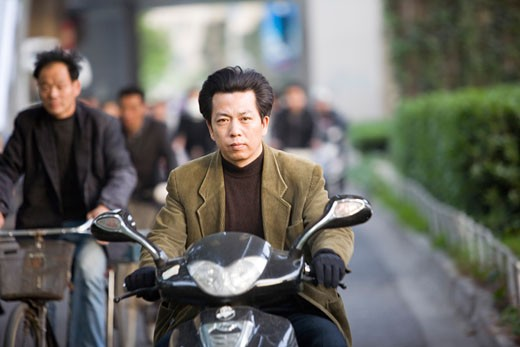 Mid adult man riding a motor scooter, Shanghai, China : Stock Photo