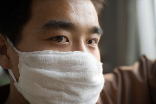 Stock Photo: 1610-354 Portrait of a young man wearing a pollution mask
