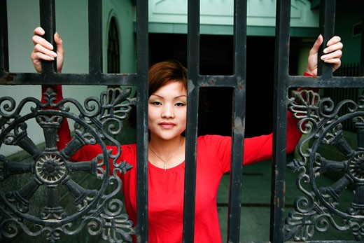 Young woman standing behind a gate : Stock Photo