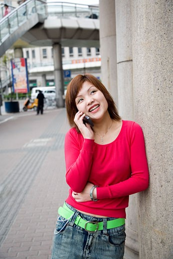Stock Photo: 1610-373 Young woman leaning against a wall and talking on a mobile phone