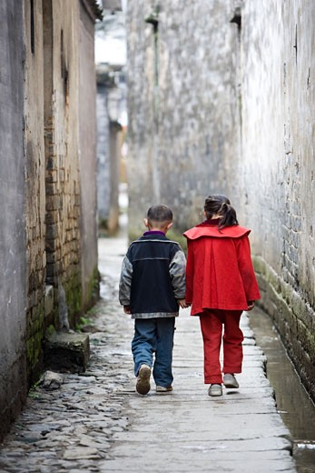 Girl and her brother walking in an alley, Cheng Kan, China : Stock Photo
