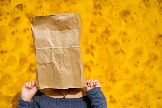 Stock Photo: 1610R-190 Close-up of a young woman covering her face with a paper bag