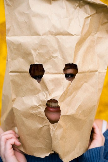 Portrait of a young woman covering her face with a paper bag : Stock Photo
