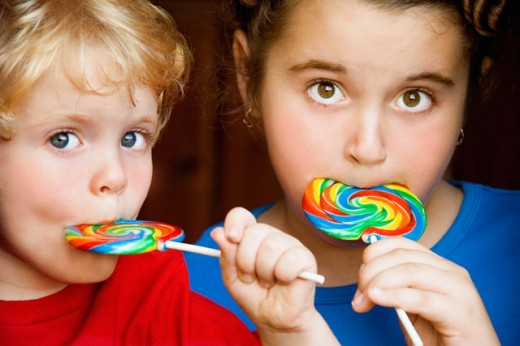 Portrait of a boy and a girl eating lollipops : Stock Photo