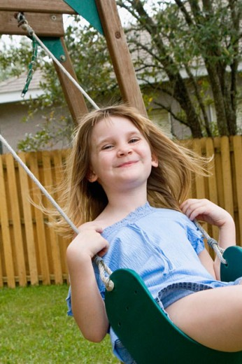 Stock Photo: 1618-248B Portrait of a girl swinging on a rope swing