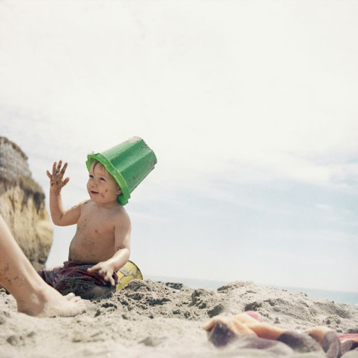 Boy with a bucket on his head playing on the beach : Stock Photo