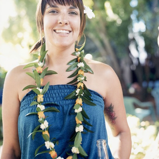 Portrait of a young woman wearing a lei and smiling : Stock Photo