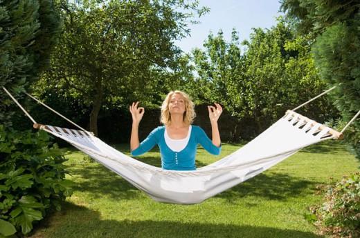 Mid adult woman meditating in a hammock : Stock Photo