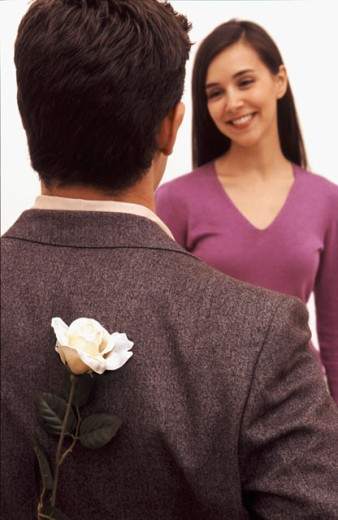 Stock Photo: 1624R-1247 A man holds a flower behind his back to surprise his girlfriend.