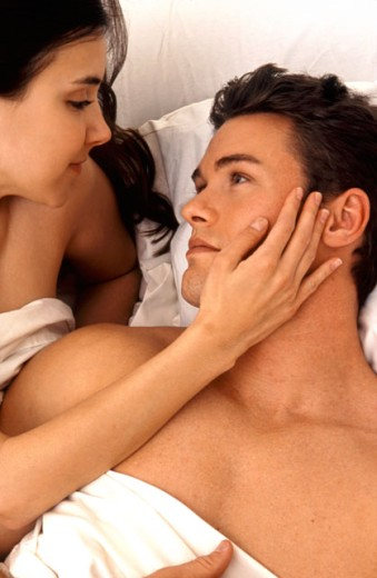 Stock Photo: 1624R-1286 Portrait of a young couple telling secrets in bed.