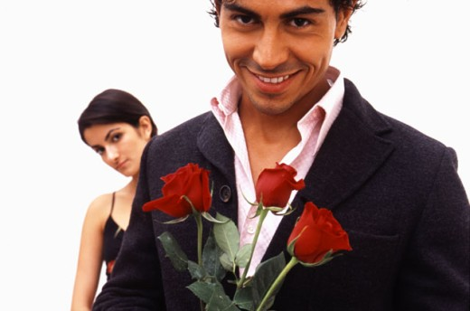 Portrait of a man holding roses with a woman behind him. : Stock Photo