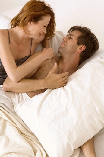 Stock Photo: 1624R-1637 Portrait of an attractive couple snuggling in bed.