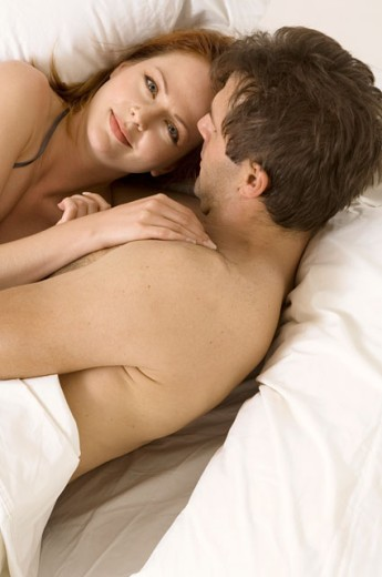 Stock Photo: 1624R-1640 Portrait of an attractive couple snuggling in bed.