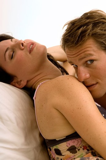 Stock Photo: 1624R-1697 Portrait of an attractive couple snuggling in bed.