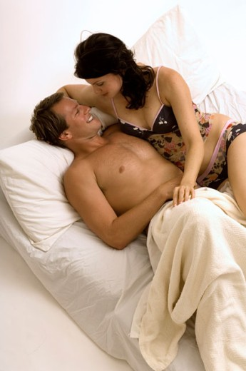 Portrait of an attractive couple snuggling in bed. : Stock Photo