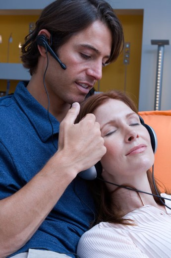 Stock Photo: 1624R-1898 Portrait of a couple snuggling while wearing headphones and ear pieces.