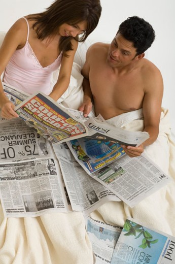 Portrait of a couple reading the newspaper in bed. : Stock Photo