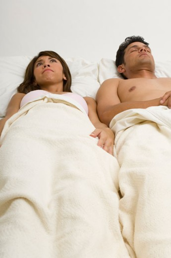 Portrait of a woman wide awake while her husband sleeps in bed. : Stock Photo