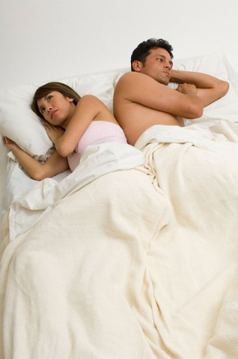 Portrait of a couple angry at each other while laying in bed. : Stock Photo