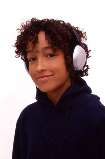 Young boy listening to music on large earphones. : Stock Photo