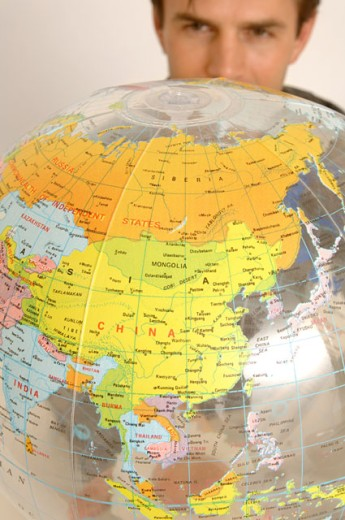 Portrait of an attractive man looking at an inflatable globe. : Stock Photo