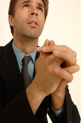 Portrait of a business man praying. : Stock Photo