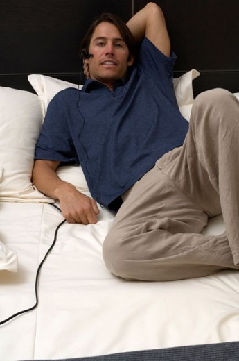 Portrait of a man lounging around in bed while on the phone. : Stock Photo