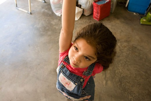 Young girl reaching for up in garage : Stock Photo