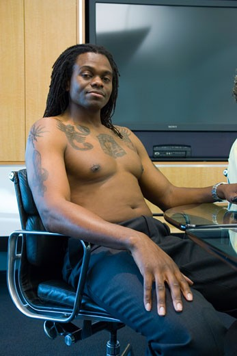 Bare-chested adult man sitting in office meeting : Stock Photo