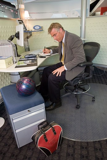 Stock Photo: 1624R-4717 Adult businessman with bowling ball on his desk