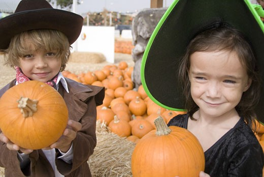 Stock Photo: 1624R-5676 Portrait of young boy and girl with pumpkins