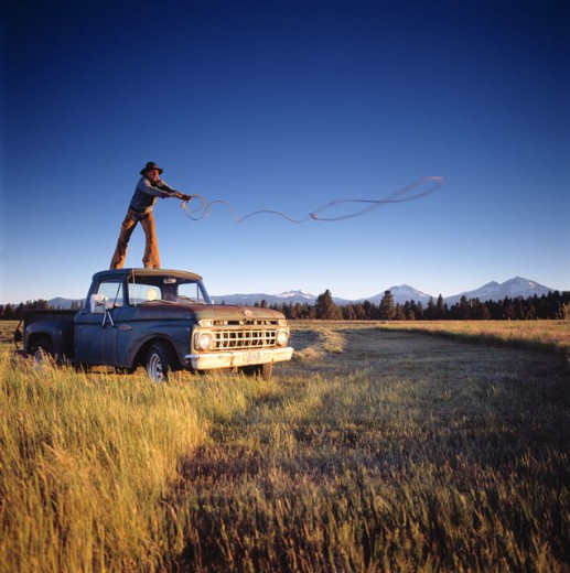 Stock Photo: 1626-2177 Cowboy Standing On A Vintage Truck In A Field And Casting A Lasso