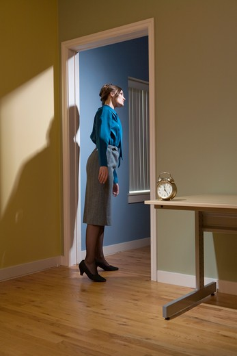 Young businesswoman standing in a doorway and looking into another room that is illuminated by light : Stock Photo