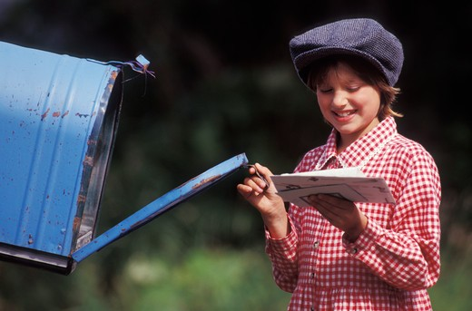 Girl retrieving letters from mailbox : Stock Photo