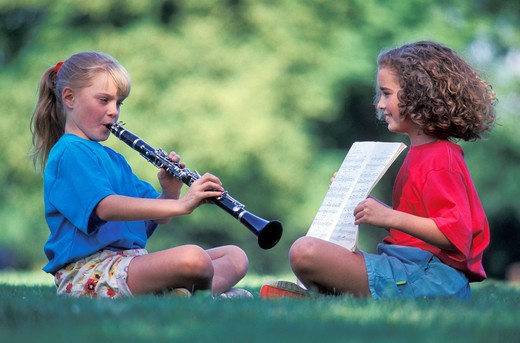 Stock Photo: 1626R-10613 Girls practicing music on grass