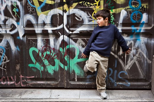 Young boy leaning against old-fashioned door covered with graffiti : Stock Photo