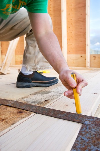 Carpenter bending and marking lumber with right angle : Stock Photo