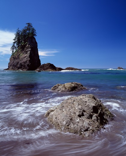 Swirling ocean water around rock with rock formation in background : Stock Photo