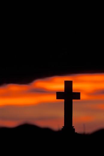 Stock Photo: 1626R-12455 Sun Setting on Lone Graveyard Cross