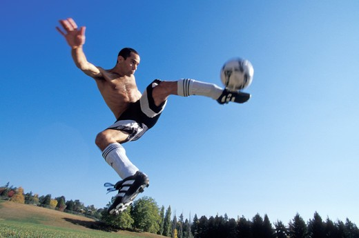 Man Kicking a Soccer Ball in Mid Air : Stock Photo