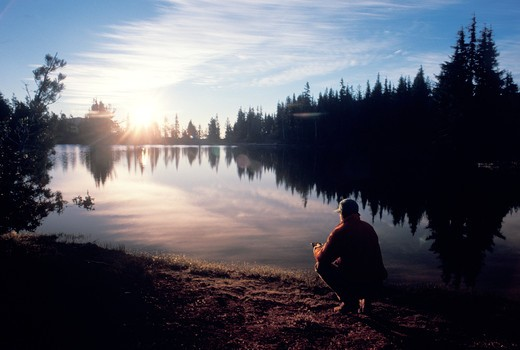 Sitting by a Mountain Lake at Sunset : Stock Photo