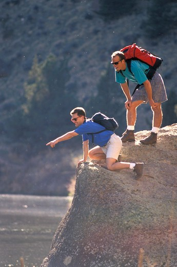 Men Standing on a Rock Pointing : Stock Photo