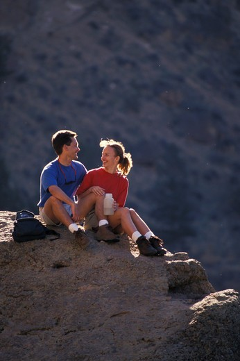 Man and Woman Sitting on a Rock Together : Stock Photo