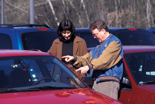Stock Photo: 1626R-13710 Couple Looking at Cars